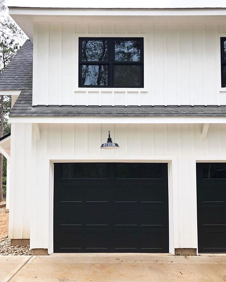 Modern Farmhouse With White Clapboard Siding Black Garage Doors And Windows And Deep Overhangs Garage Doors Black Garage Doors Garage Door Design