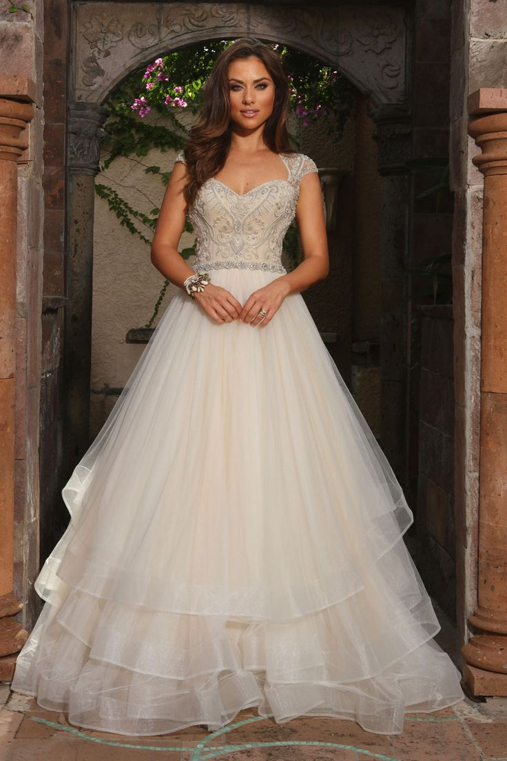 BALL GOWN WITH DRAPED LAYERS SKIRT, BEADED CAP SLEEVES AND BODICE WITH ILLUSION BACK.