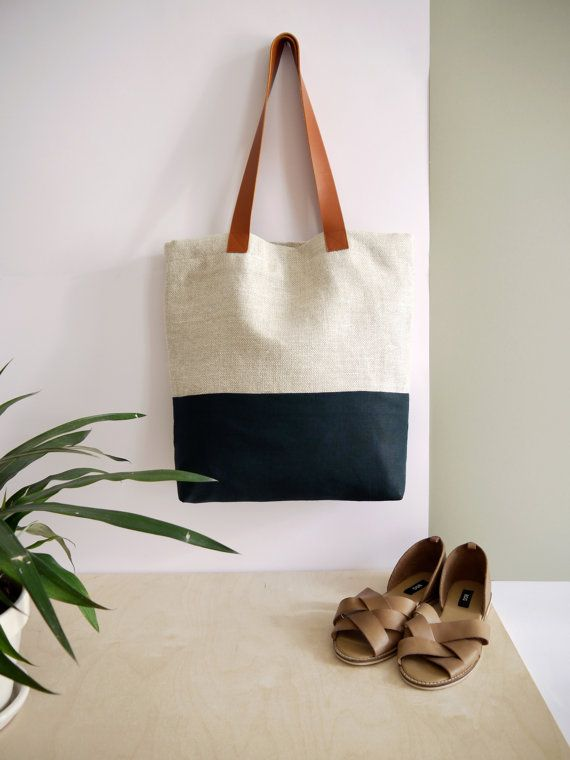 Handbag tote shape, made in beige linen with navy linen band.    The handles of the bag are made of genuine leather Fauve colors.    The bag is fully