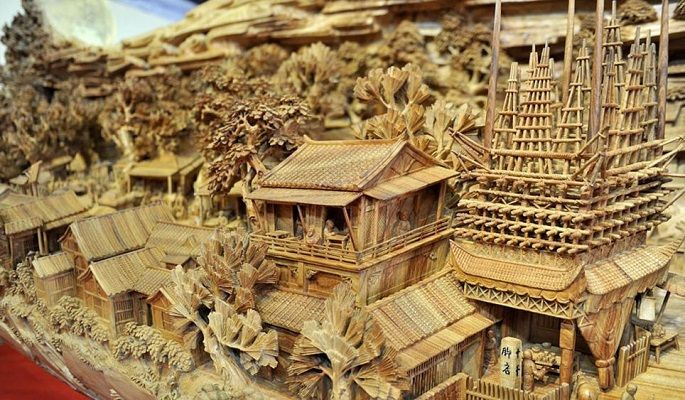 """Chinese woodcarving by sculptor Zheng Chunhui called """"Along the River During the Quinming Festival"""" and is a replica of a famous 1,000 year old Song Dynasty scroll painting."""