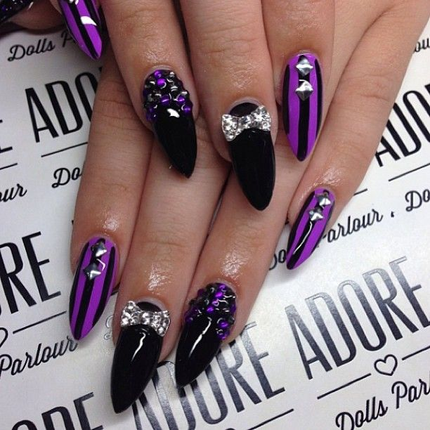 Purple and black stiletto nails with studs and bows