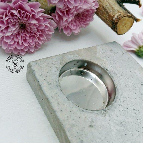 Szögletes beton mécsestartó - 4190 Ft  Betonból készült, modern tárgy teamécsesnek. Azoknak ajánlom, akik a betont nyers valójában, érdes felületével, csupaszon szeretik.  Szigorúságát a szögletes forma és a fém betét hangsúlyozza. A tárgy méretei: szélessége: 9 cm, mélysége: 9 cm, magassága: 1,5 cm