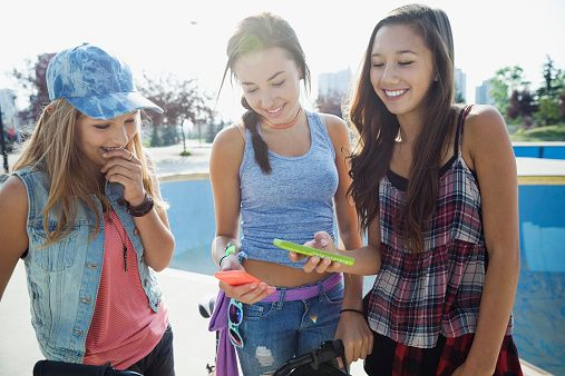 Teenage girls with cell phones at skateboard park