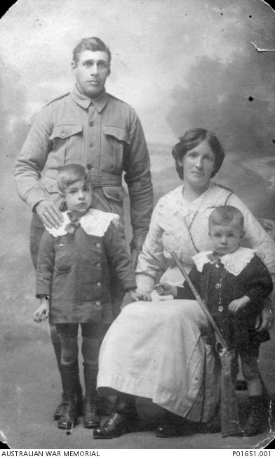 Studio portrait of 2919 Private (Pte) Alfred John Henry (Alf) Lovett, of Hamilton, Vic, an Aboriginal serviceman, with his wife Sarah and two sons. A rifle is propped up against Mrs Lovett's leg. Pte Lovett ,a member of the 6th Reinforcements of the 26th Battalion, embarked from Melbourne on 27 October 1915 aboard HMAT Ulysess. He later transferred to the 12th Battalion and returned to Australia on 10 March 1918.