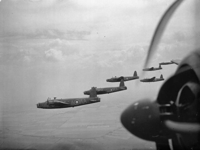 Vickers Wellington Mark IAs and ICs of No. 75 (New Zealand) Squadron RAF based at Feltwell, Norfolk, flying in loose formation over the East Anglian countryside. The New Zealand Wellington Flight was elevated to squadron status as No. 75 in April 1940, the first such Commonwealth unit in Bomber Command. The leading aircraft in the formation, P9206 'AA-A', was usually flown by the Squadron's Commanding Officer, Squadron Leader C E Kay. © IWM (CH 467)