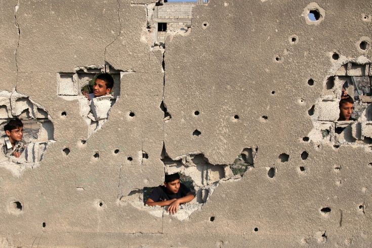 Palestinian children look out from their family's house, which witnesses said was badly damaged during the recent Israeli offensive, in the east of Gaza City on Aug. 28, 2014. (Majdi Fathi/NurPhoto/Zuma Press)