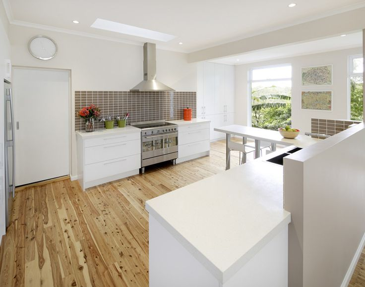 this all white kitchen was adorned with hardwood floors and brown kitchen backsplash tiles.