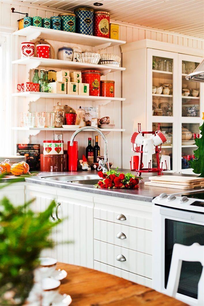 TRADITIONELLT JULHEM MED TWIST: Ännu syns ingen snö så långt ögat når. Men att det snart är jul är det ingen tvekan om. Familjen Malmquist-Viippolas hus strålar av julstämning också om luften är disig. På trappan står granar i krukor och korgar, och i fönstren hänger julstjärnor. [...]Hyllorna i köket är fyllda av vackra plåtburkar som Anna hittat på loppis. Vitrinskåp, Ikea. Köksinredning från Kök & Bygglagret. Trähyllorna har Anna och Teuvo själva snickrat   Hus & Hem - via Bettina Holst