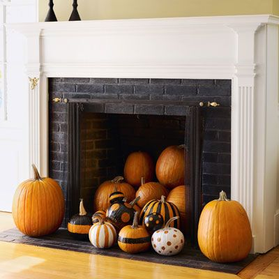 Instead of the usual haunts, try grouping pumpkins in a less-expected locale, like an unused fireplace. This to-die-for arrangement mixes plain and painted varieties for maximum eye appeal. For the graphic gourds, use painter's tape and self-adhesive paper to mark off stripes and circles. Spray with glossy black and white paint, then casually heap in the hearth.
