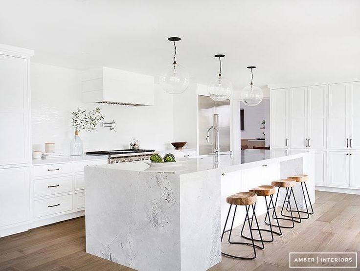 Exquisite kitchen features three clear glass globe pendants illuminating a white marble island fitted with a farmhouse sink and pull out faucet lined with Wisteria Smart & Sleek Stools.