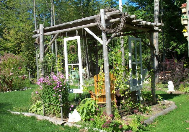 Basic garden shade structure made from freely swinging old salvaged windows