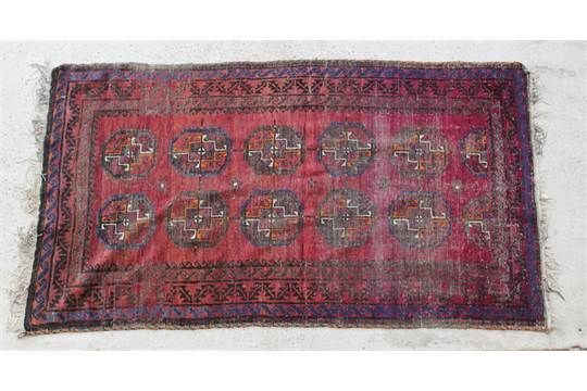 A red and blue Afghan rug with medallions to the centreThis lot has some wear