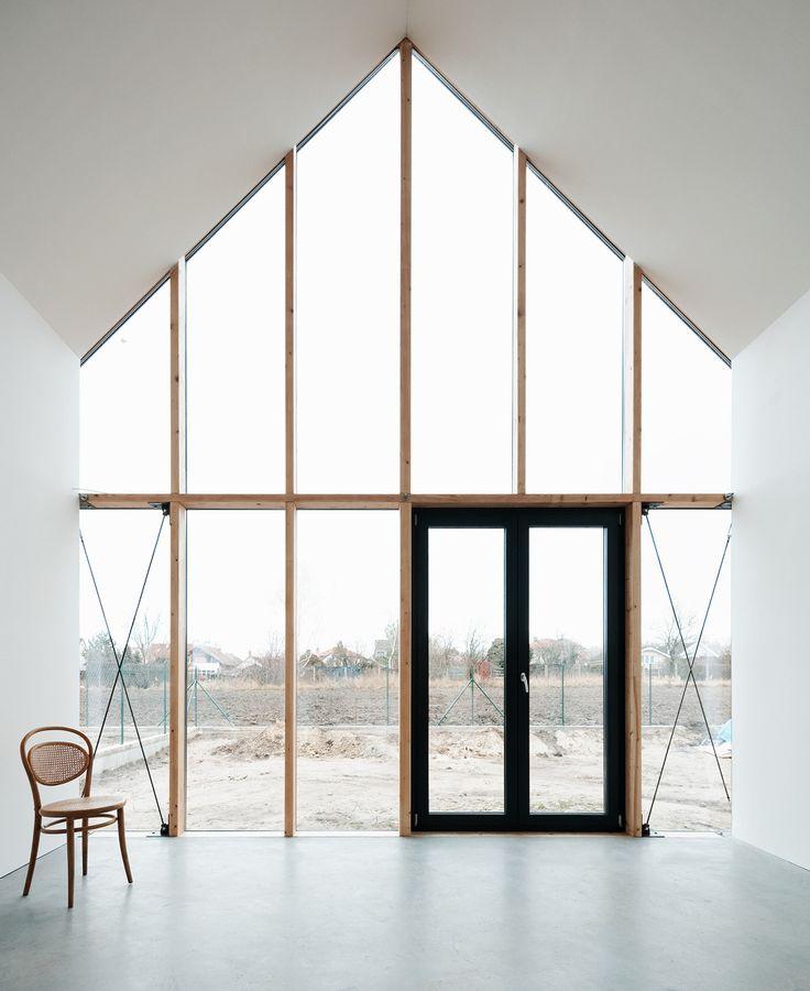 black door + concrete floor + white walls + window wall + pitched ceiling