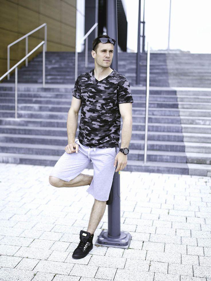 Streetowo-militarny outfit Denley dla aktywnych. Szare krótkie spodenki są bardzo wygodne, T-shirt w serek we wzór moro przyciąga spojrzenia, a klasy stylizacji dodają okulary, zegarek i najmodniejsze od paru sezonów sneakersy.
