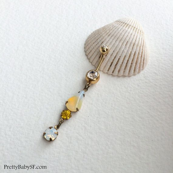 gold belly ring, opal belly ring,yellow belly ring,swarovski,citrine,jonquil,Belly button ring,bellybutton ring, dangle belly ring,vintage  PLEASE SEE SHIPPING TAB FOR TURNAROUND TIME  Pretty belly ring in surgical steel colored GOLD with a double gem in CLEAR with vintage swarovski and rhinestone brass prong set glass crystal dangles in jonquil, and yellow, opalescent, and opal clear  entire piece approx 2 3/8 long. / 6 cm 14 gauge Large barbell rhinestone approx 7mm across  Comes in an…