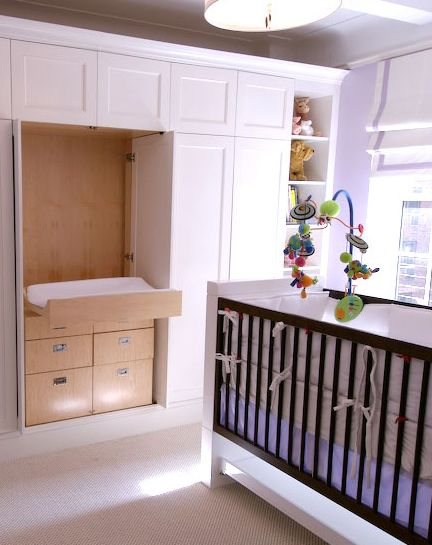 nursery with built in fold out changing area and drawers in closet