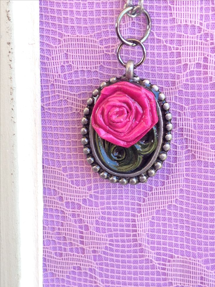 Hand folded paper rose necklace coated in resin.