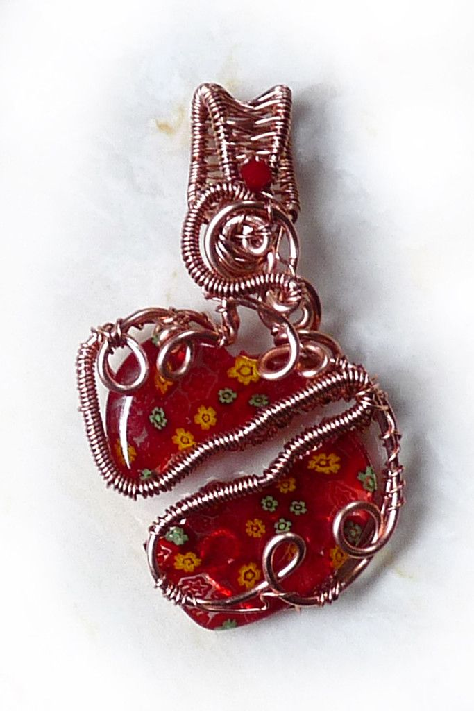 Hearts and Flowers. This one-of-a-kind wire wrapped pendant features a mille fleur glass heart that's been broken in two and reset in a bright copper wire wrap. The heart is literally woven back together in an abstract coiled and woven design. This pendant is a piece of truly unique, 3-dimensional wearable art. #valentine #heart