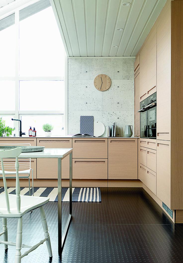 Køkkenet i hvidtonet egetræ får råt modspil af industrielle strukturer og overflader som bordplade i Silestone, et sort gummigulv og vægge med betonlook.