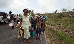 Local residents carry their belongings along a road.