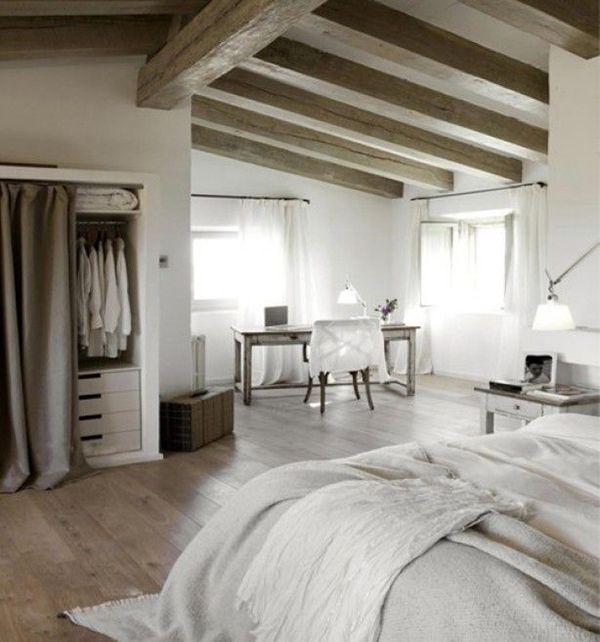 Grote #landelijke #slaapkamer met veel ruimte. Schuin #plafond met #houten balken, #kledingkast achter een #gordijn en een gezellig hoekje met een #oud #bureau. #rustic #bedroom