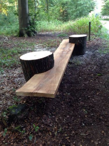build your own garden bench using tree stumps and a long piece of wood.