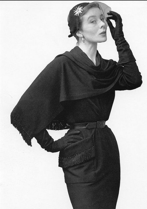 1950 Bettina in belted black jersey dress adorned with fringed pocket and fringed shawl by Nina Ricci,