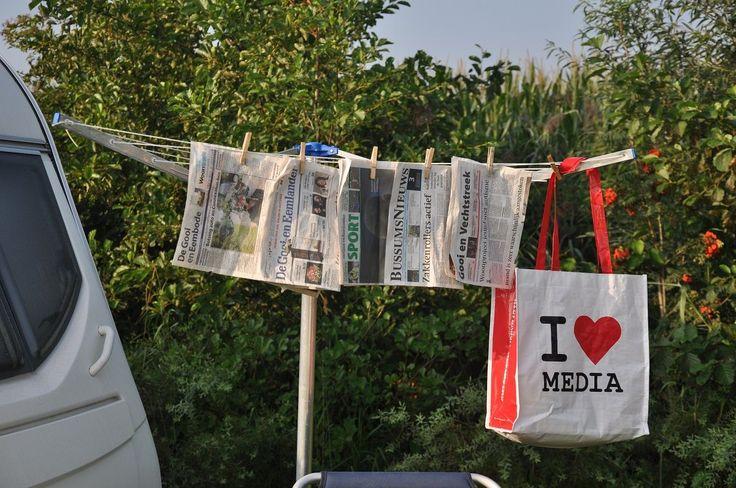 Verregende regionale kranten op de camping. Ook de I love Media tas moest even drogen. Foto: Ineke van Loon
