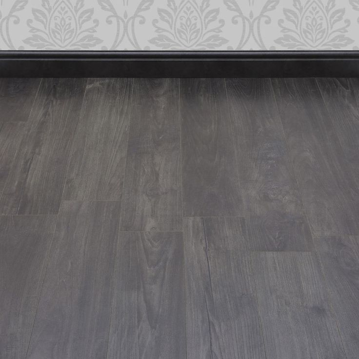 Dark grey tones and a gorgeous wood effect texture make this Manor Nostalgic Teak Graphite laminate floor a must-have for a modern home that requires a striking décor addition at a great price. The embossed surface and the wonderfully reproduced saw marks and organic lines offer an impressive level of authenticity.  Measuring 193mm in width and featuring V-groove edging, the planks will suit rooms of any size. An 8mm thickness provides a comfortable feel underfoot and ensures that the floor…