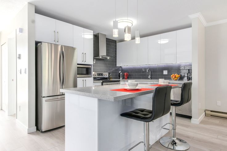 White kitchen with grey backsplash and red colour accessories