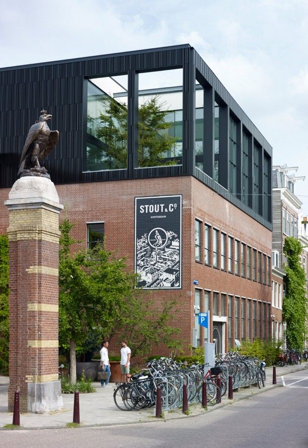 Dans les rues d'Amsterdam, au-dessus d'un bâtiment typique en brique, se trouve cette boite noire mystérieuse baignée de lumière, à l'intérieur de laquelle