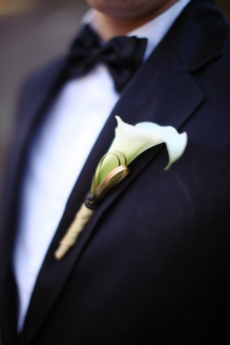 white calla lily boutonniere with added branches behind in either silver or gold (silver for Yuri, gold for the rest of the men)