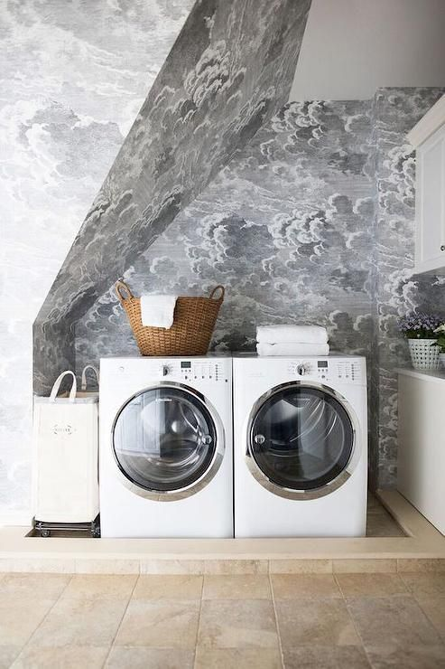 Charming white and gray laundry room boasts sloped walls accented with stunning Nuvole Storm wallpaper from Cole & Son while a steel vertical canvas laundry bin from Crate & Barrel is sat against the wall beside a white front loading washer and dryer topped with a woven laundry basket.