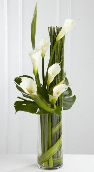 Eternal friendship vase arrangement - a stylized vase arrangement of white calla lilies and assorted foliages.