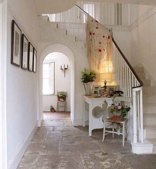 Foyer with stone floor painted staircase and arched for Country foyer ideas
