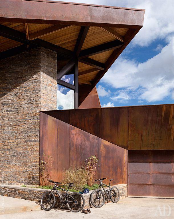 Пристроенный к дому гараж выдержан вобщей стилистике: такой же геометричный иотделансталью.