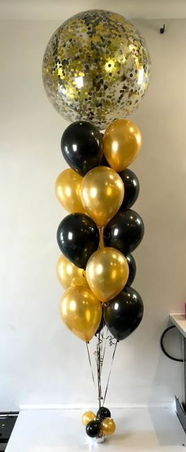 3ft confetti balloon paired with a whole bunch of latex balloons in gold and black.