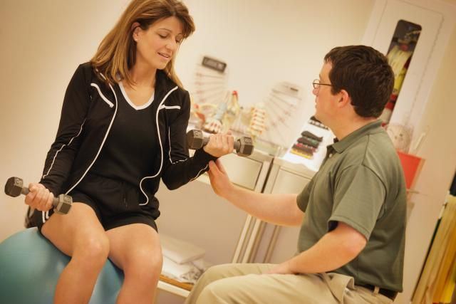 What You Should Know About Becoming an Occupational Therapist: An occupational therapist does strengthening exercises with a patient.