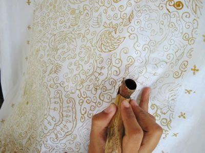 Batik wax outline being  added to fabric in the traditional Javanese fashion.