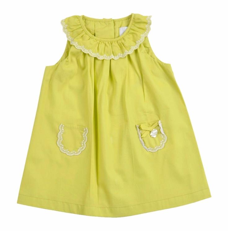 Vestido para Bebe Niña confeccionado en algodón 100%, en color verde limón. Cuello redondo y sin mangas. Del cuello sale un vuelo semi fruncido, en color verde de la misma tela del Vestido y con encaje blanco en el borde. Al frente del Vestido dos pequeños bolsillos con encaje en el borde, y un lacito en uno de ellos. Se abotona en la espalda.