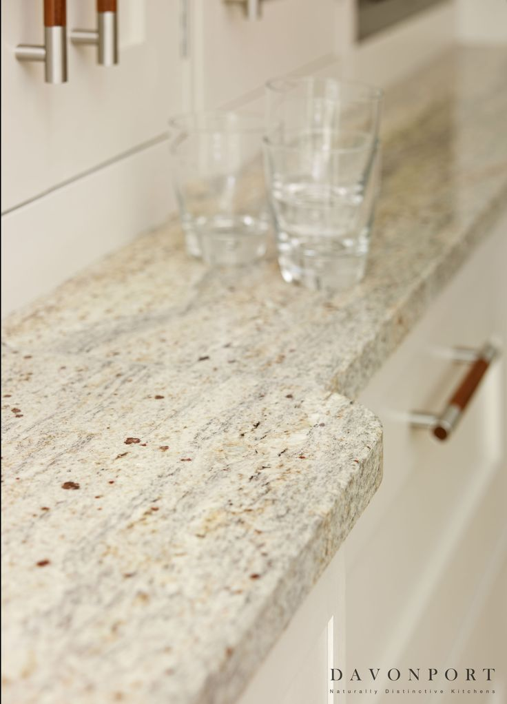 The Kashmir White granite worktops are perfectly in keeping with the light, contemporary theme of the design. The brown flecks give a gently nod to the walnut accents in the room such as the handles and curved breakfast bar.