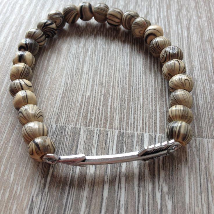 Armband van 7mm wit hout met zwarte strepen en een metalen pijl. Van JuudsBoetiek, te bestellen op www.juudsboetiek.nl.