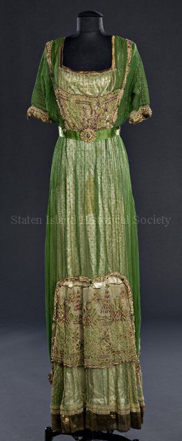 Evening Dress, ca. 1910, by Redfern. Three layers of fabric: top layer is green chiffon; middle layer is gold metallic net with round gold beads; lining is ivory silk satin. Waist is defined by a green silk ribbon with 4 beaded medallions that have green plastic scarabs in the center.