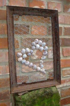 Ein rechteckiger, rostiger, gusseiserner Ofenrahmen vom Schrottplatz erhielt eine doppellagige Füllung aus Hasendraht. Ich klemmte den Draht einfach in einer Rille des Rahmens fest. Das hielt. Nun noch ein paar leere Schneckenhäuser mit Heißkleber auf den Draht geklebt und fertig ist das Gartenbild für den Sims an der Backsteinmauer. (79 …