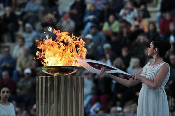 Actress Ino Menegaki plays a high priestess as she lights a torch with the Olympic flame on October 5, 2013 at the Panathenaic stadium in Athens during a handover ceremony of the Olympic flame for the the Sochi 2014 Olympic Winter Games which begin on February 7. AFP PHOTO / LOUISA GOULIAMAKI (Photo credit should read LOUISA GOULIAMAKI/AFP/Getty Images)