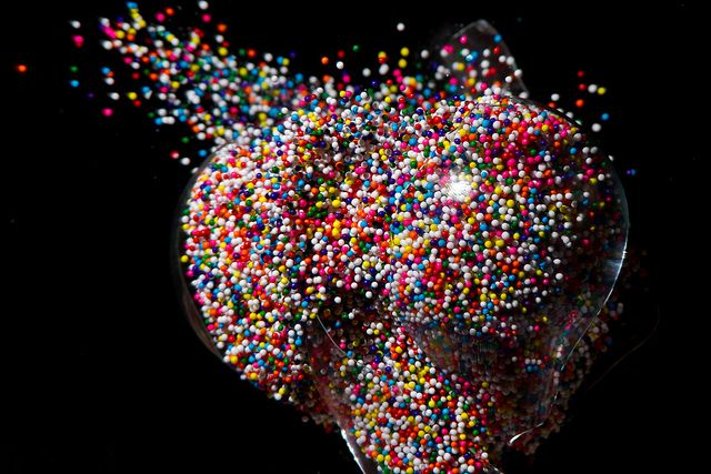 Chemist and photographer Jon Smith fills light bulbs with unusual objects like chalk dust, candies, sprinkles, or even beer caps, shoots the bulbs with a pellet gun, and captures the moment using high-speed photography.