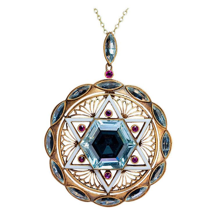 Art Deco Star of David Aquamarine Pendant. An original pre World War II Art Deco pendant designed as a round openwork matte gold plaque with a white enamel six pointed Star of David set with a hexagonal aquamarine and six small rubies. The star is flanked by six Art Deco openwork floral ornaments encircled by twelve navette cut aquamarines.  c 1930
