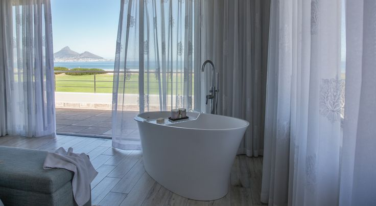 The free standing resin bath on the Antique wood look porcelain tiles with the view of Table Mountain makes this a romantic bathroom with a great view.