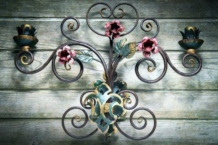 Lampada MOIRA | Applique in ferro battuto artistico con fiori e foglie e giglio, dipinta con colore all'acqua, steso a mano e poi cerato. Supporto per 2 lampade (non comprese). Cablaggio elettrico eseguito con materiali certificati. Altezza: +/- cm 38. Larghezza: +/- cm 52. #wroughtiron #Dolomites #Craftsmen #MadeInItaly