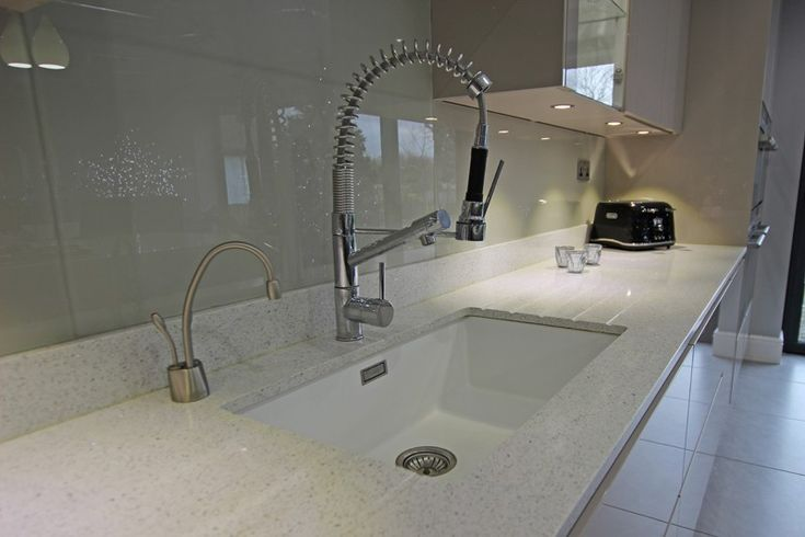 Lactea Compac Quartz worktop and kitchen upstand, combined with a glass kitchen splashback